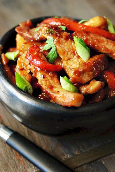 Zoete reepjes varkensvlees met rode paprika en lente-uitjes